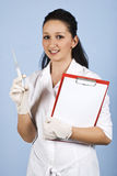 Young medical student. Female smiling and  holding a syringe and a clipboard on blue background,check also  Medical Royalty Free Stock Photography