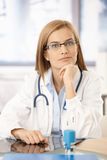 Young medical student sitting at desk in office. Smiling, wearing glasses stock image