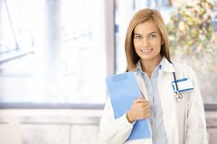 Young medical student smiling in office. Young attractive medical student smiling in office, holding folder Royalty Free Stock Image