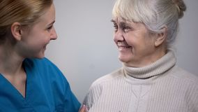 Young medical worker talking with smiling elderly lady in hospital, good news stock photography