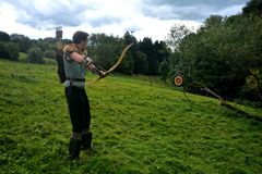 Young medieval archer with chain shirt, bow and arrow in nature during sheet tensioning Royalty Free Stock Photos