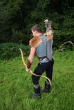 Young Medieval archer with chain shirt reaches for arrow, with bow in hand Royalty Free Stock Images