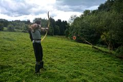 Young medieval archer if target aims with arrow and curve at straw Stock Photography