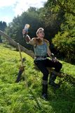 Young Medieval dressed man, holds drinking horn high in the hand, looks upwards. And sits on branch in the nature , arrow and curve stands besides Royalty Free Stock Photography