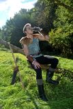 Young Medieval dressed man, sits on branch, drinks from drinking horn Stock Photography