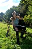 Young Medieval dressed man, sits on branch, drinks from drinking horn. Eyes open, arrow and curve stands besides Royalty Free Stock Image