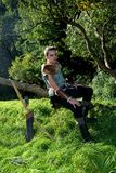 Young Medieval dressed man, sits on branch, hands on legs , arrow and curve stands besides. Young Medieval dressed man, sits on branch, hands on legs and looks Stock Photography