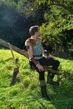 Young Medieval dressed man, sits on branch, hands on legs and looks to the back. Arrow and curve stands besides Royalty Free Stock Images