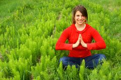 Young meditating in a field. A young girl meditating in a field Royalty Free Stock Photo
