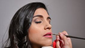Stylist painting the lips with a lip brush stock footage