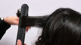 Hairdresser combing and curling a young girl`s hair stock video footage