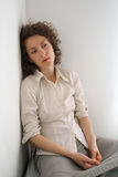 Young melancholic woman. Sitting and thinking royalty free stock photos