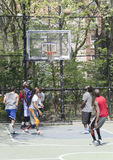 Young men in action playing basket ball in the street Royalty Free Stock Photos