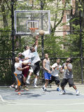 Young men in action playing basketball in the street Royalty Free Stock Image
