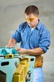 Young men adjusts woodworking mashine Stock Photos