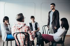 Young man admitting that he is an alcoholic during support group meeting royalty free stock photography
