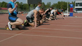Young men athletes start to sprint 100 meters in stadium