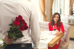 Young couple having romantic dinner in the restaurant surprise blurred. Young men back view making a surprise and women sitting smiling having romantic dinner in Royalty Free Stock Photo