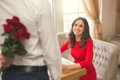 Young couple having romantic dinner in the restaurant surprise. Young men back view making a surprise and women sitting smiling having romantic dinner in the Stock Images