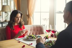 Young couple having romantic dinner in the restaurant using smartphone angry. Young men back view and women angry browsing smartphone having romantic dinner in Stock Photo