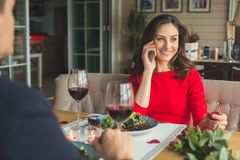 Young couple having romantic dinner in the restaurant phone call happy. Young men back view and women phone communication smiling having romantic dinner in the Royalty Free Stock Image