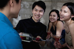 A young men bartender serving drinks to group of friends Stock Images