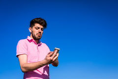 Young men being curious about the phone. Young man being curious about the phone features stock photos