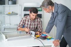 Young man being supervised while calibrating air conditioner Royalty Free Stock Photos