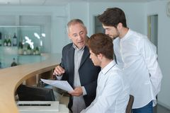 Young men being trained at reception desk. Training royalty free stock image