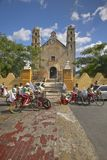 Young men bicycle in front of Catholic cathedral of Izamal and light torch in the Yucatan Peninsula, Mexico Stock Photography