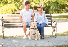 Young man and blind woman with guide dog sitting. Young men and blind women with guide dog sitting on bench in park royalty free stock photos