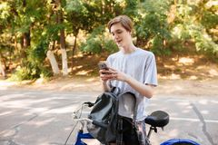 Young man with blond hair standing with backpack and bicycle in park. Cool smiling boy standing and using his cellphone. Young men with blond hair standing with Royalty Free Stock Image