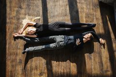Conceptual photography. Actor play. Hard shadows. A young men and young blonde women with long hair lying on the floor. Problems and difficulties in relations stock images