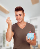 Young men with a blue moneybox Stock Photography