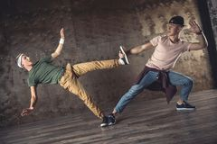 Break Dance. Young men break dancing on the wall background, performing tricks stock images