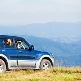 Romantic trip to the mountains. The young men in car looking at the Carpathian Mountains through binoculars Stock Photos