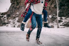 Young man carries his girlfriend on back across puddle of melted water with splashes . Young men carries his girlfriend on back across puddle of melted water Royalty Free Stock Photo