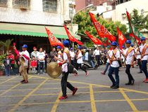 Young Men Carry Flags and Beat Gongs Stock Photography