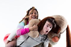 Young man carrying woman with big plush animal. Young men carrying women with big plush animal against white background stock photos