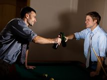 Young men clinking beer bottles at snooker Stock Images