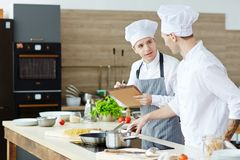 Young men cooking. Young men consulting about cooking procedure with chef in the kitchen royalty free stock photography