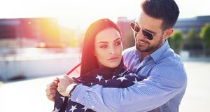 Young man covering woman with USA flag in sunset stock photography