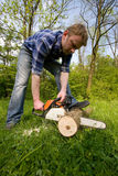 Young men is cutting wood. By chain saw stock photos