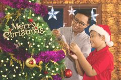 Young man decorating fir tree with his son. Young men decorating fir tree with his son while celebrating Christmas at home stock photos