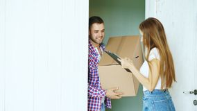 Young man deliver cardboard box to customer at home. Woman sign in clipboard for receiving parcel Stock Photo