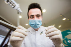 Young men dentist with sterile mask readily approaching a patient with dental instruments held in the hands protected with surgica Royalty Free Stock Photos