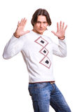 Young men dressed in modern clothes. In a sweater and jeans. The guy raise their hands up. Shows palms Stock Image