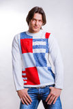 Young men dressed in modern clothes. In a sweater and jeans Stock Image