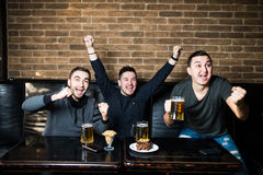 Young men drink beer, eat snaks and cheering for football match. Winning emotions. Royalty Free Stock Photos
