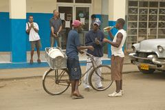 Young men drinking alcohol from bottle in front of old cars and old stores in Cuba, near the El Rincon Royalty Free Stock Images